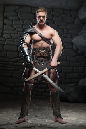 praetorian: Full length portrait of young attractive warrior gladiator with muscular body posing with two swords on dark background  Concept of masculine power, strength