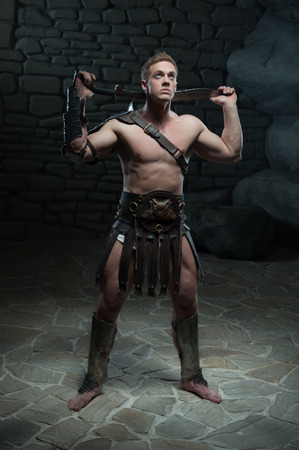 praetorian: Full length portrait of young attractive warrior gladiator with muscular body posing with sword on dark background  Concept of masculine power, strength