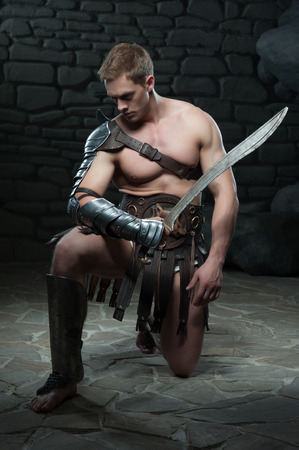 praetorian: Full length portrait of young attractive warrior gladiator with muscular body kneeling with sword on dark background  Concept of masculine power, strength Stock Photo