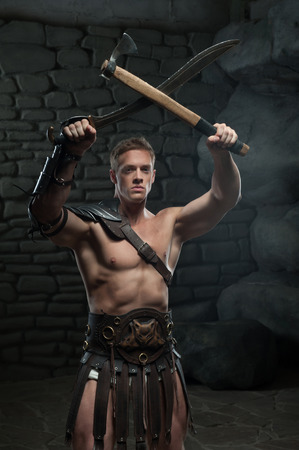 strong toughness: Half length portrait of young attractive warrior gladiator with muscular body holding sword and axe on dark background  Concept of masculine aggressive power, strength