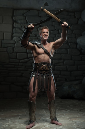 praetorian: Full length portrait of young attractive warrior gladiator with muscular body holding sword and axe on dark background  Concept of masculine aggressive power, strength