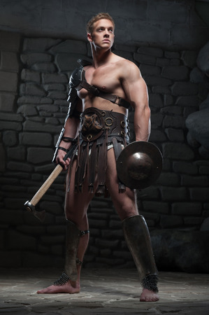 the romans: Full length portrait of young attractive warrior gladiator with muscular body holding shield and axe, posing on dark background  Concept of masculine power, strength Stock Photo