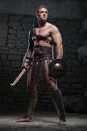 romano: Retrato de cuerpo entero de la joven y atractiva guerrero gladiador con cuerpo musculoso sosteniendo el escudo y el hacha, que presenta en el fondo oscuro Concepto de poder masculino, la fuerza Foto de archivo