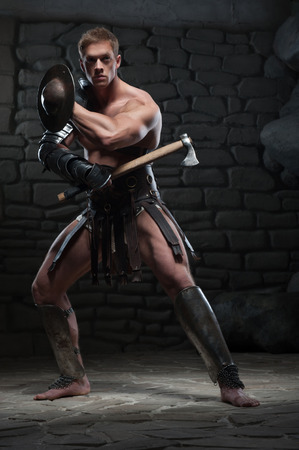 praetorian: Full length portrait of young attractive warrior gladiator with muscular body holding shield and axe, posing on dark background  Concept of masculine power, strength Stock Photo