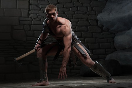 Full length portrait of young attractive warrior gladiator with muscular body holding axe