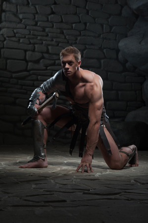 praetorian: Full length portrait of young attractive warrior gladiator with muscular body holding axe, kneeling on dark background  Concept of masculine power, strength