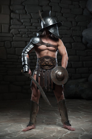 Full length portrait of warrior gladiator with muscular body in helmet holding sword on dark background  Concept of masculine power, strength Stock Photo