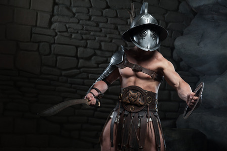 Half length portrait of warrior gladiator with muscular body in helmet holding sword on dark background  Concept of masculine power, strength