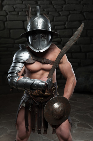 Half length portrait of warrior gladiator with muscular body in helmet holding sword on dark background  Concept of masculine power, strength photo