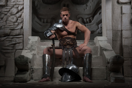 strong toughness: Full length portrait, gladiator in armour sitting on steps of ancient temple with helmet and sword, on dark background  Concept of masculine power and strength