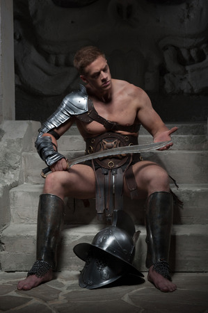 strong toughness: Full length portrait, gladiator in armour sitting on steps of ancient temple looking at sword, on dark background  Concept of masculine power and strength