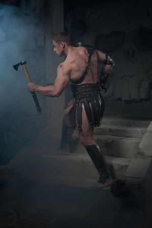 strong toughness: Full length portrait of young handsome muscular man gladiator in armour running up stairs of ancient temple with sword and axe in smoke, concept of power, aggression, masculinity