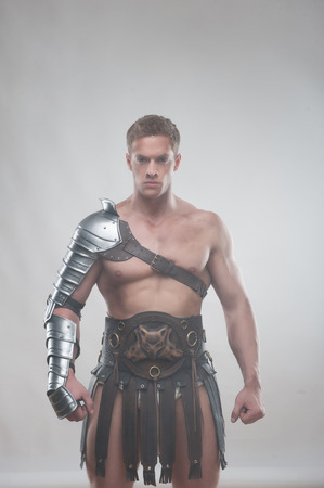 praetorian: Half length portrait of young handsome muscular man gladiator in armour posing isolated over grey background, concept of masculinity, determination, strength Stock Photo