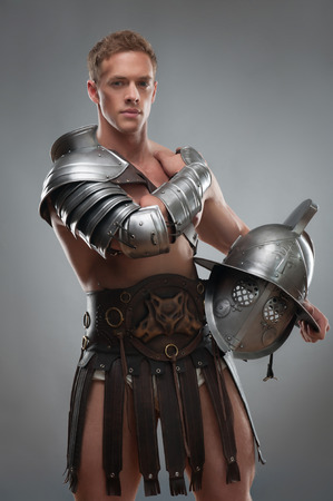 Half length portrait of young handsome muscular man gladiator in armour posing with helmet isolated over grey background