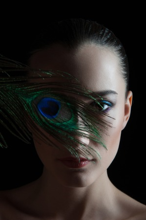 Beautiful brunette young woman with peacock style make-up and peacock feather isolated on black background photo