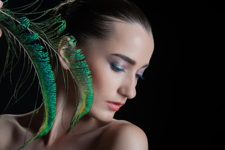 Beautiful brunette young woman with peacock style make-up and peacock feather, sideview  portrait isolated on black background photo