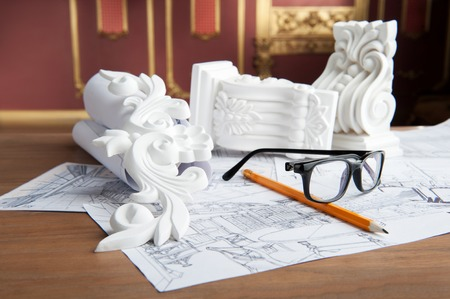 moulding: Closeup portrait of spectacles, yellow pencil, design drawing and white stucco moulding, on wooden table over classical interior at studio shot Stock Photo