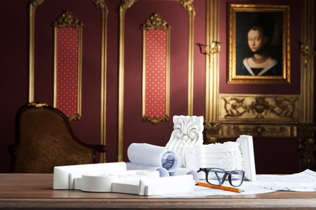 moulding: View of spectacles, yellow pencil, design drawing and white stucco moulding, on wooden table over classical interior at studio shot