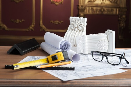 moulding: Closeup portrait of spectacles, yellow pencil, design drawing and tape measure and white stucco moulding on wooden table over classical interior, studio shot Stock Photo