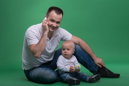 Happy handsome Caucasian father sitting on the floor with his son baby boy playing with toy cellphone, isolated on green photo