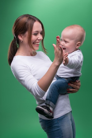 Half length portrait of young attractive Caucasian mother and cute baby smiling and giving high five, isolated on green