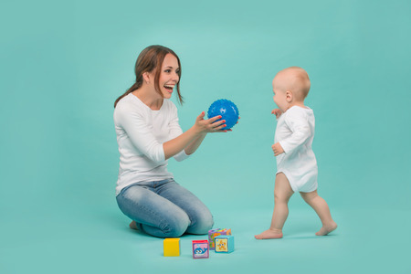 Young Caucasian attractive smiling mother playing with her cute little son with a ball and colored blocks, baby boy wearing bodysuit running isolated on blue photo