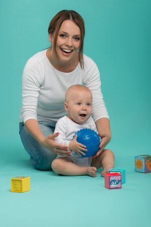 Young Caucasian attractive smiling mother playing with her cute little son with a ball and colored blocks, baby boy wearing bodysuit, mom embracing baby, isolated on blue