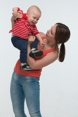 cranky: Portrait of young attractive mother holding her screaming toddler son being naughty and cranky, isolated on white