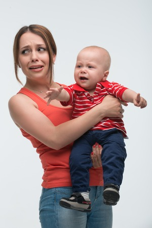 Portrait of young attractive mother holding her screaming toddler son being naughty and cranky, isolated on white