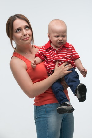 Portrait of young attractive mother holding her screaming toddler son being naughty and cranky, isolated on white photo