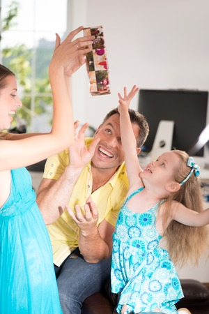 Family sideview portrait, cute little girl having fun with presents and packs, beautiful blonde mom lifting presents, laughing daughter and father trying to catch them at home interior photo