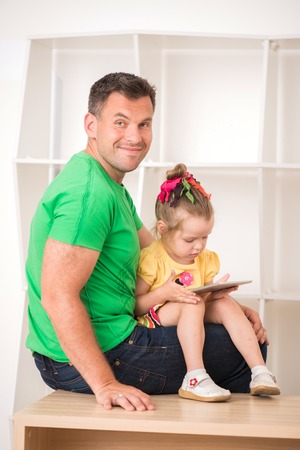 Half-length portrait of happy smiling father and child using electronic tablet at home sitting on desk photo