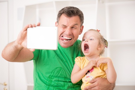 Closeup portrait of happy smiling father and child using electronic tablet at home making selfie, having fun and playing fool photo