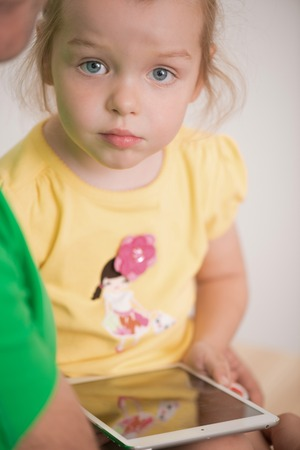 Full length portrait of cute little girl, adorable child using electronic tablet at home sitting on fathers hands photo