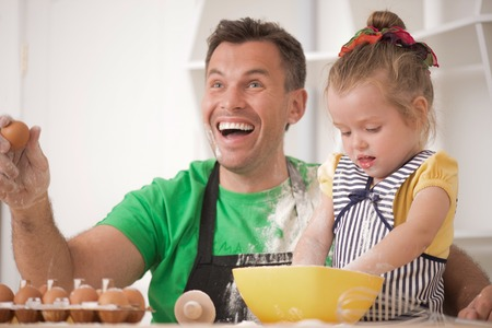 Half-length portrait of cute little daughter with happy handsome father cooking pastry, mixing flour and having fun  Kid throwing flour at father photo