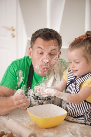 Half-length portrait of cute little daughter with happy handsome father cooking pastry, mixing flour and having fun photo
