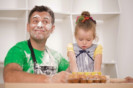 Half-length portrait of cute little daughter with happy handsome father cooking pastry, mixing flour and having fun, low angle photo