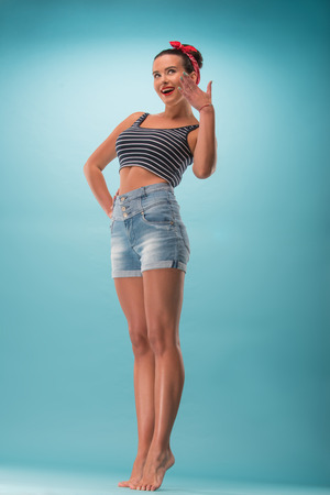 Full length portrait of beautiful girl with pretty smile in pin-up style posing with hand by her cheek isolated on blue background