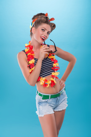 coquette: Half length portrait of beautiful emotional coquette girl with pretty smile in pinup style with Hawaiian flowers necklace posing with sunglasses isolated on blue Stock Photo