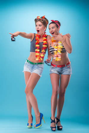 Full length portrait of two beautiful emotional coquette girls with pretty smiles in pinup style with Hawaiian flowers necklaces amazed pointing at something and laughing isolated on blue Stock fotó
