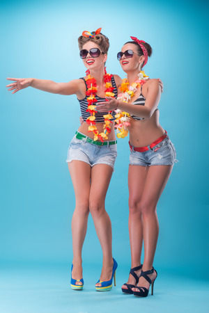 coquette: Full length portrait of two beautiful emotional coquette girls with pretty smiles in pinup style with Hawaiian flowers necklaces, stretching hands meeting somebody and laughing isolated on blue