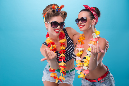 Full length portrait of two beautiful emotional coquette sexy girls with pretty smiles in pinup style with Hawaiian flowers necklaces, inviting somebody with finger isolated on blue Stock Photo