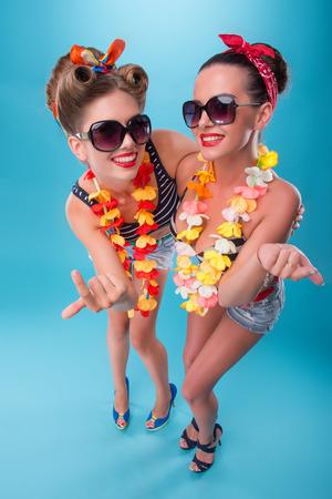 coquete: Retrato da vista superior de dois belos coqueiros emocional meninas sexy com sorrisos bonitos em estilo pinup com flores havaianas colares, convidando algu