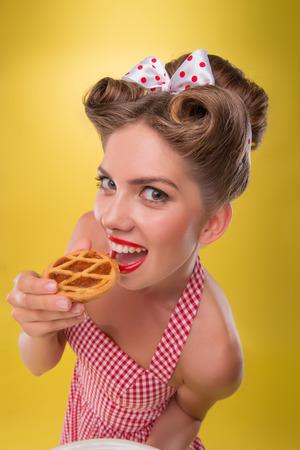 coquete: Top retrato opini�o do close up da menina bonita coquette no vestido com sorriso no estilo pinup comer um bolinho isolado no amarelo