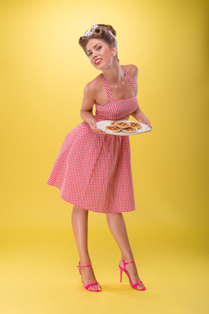 Full length portrait of beautiful coquette girl in dress with pretty smile in pinup style posing with tray of cookies isolated on yellow