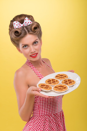 coquette: Half length portrait of beautiful coquette girl in dress with pretty smile in pinup style posing with tray of cookies isolated on yellow