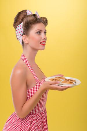 coquete: Meio comprimento vista lateral retrato da menina bonita no vestido coquette com sorriso no estilo pinup posando com bandeja de biscoitos isolado em amarelo