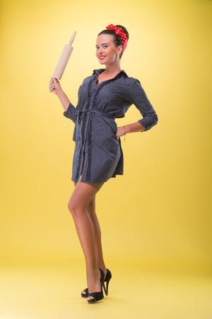 coquete: Retrato cheio do comprimento da menina bonita sexy com sorriso no estilo pin-up que levanta com o rolo da massa, coquette sexy em meias, isolado no amarelo
