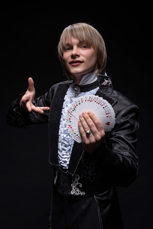 Half-length portrait of fair-haired matchless juggler wearing interesting black costume and white shirt showing us different tricks with cards  Isolated on black background photo