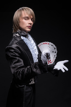 Half-length portrait of fair-haired serious juggler wearing interesting black costume and white shirt standing aside conjuring with the pack of cards in his hand  Isolated on black background photo